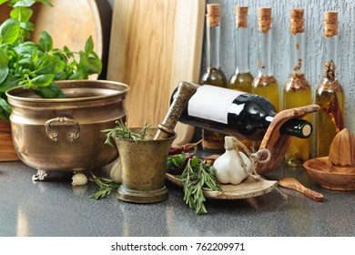 Kitchen utensils with basil and bottles of olive oil.