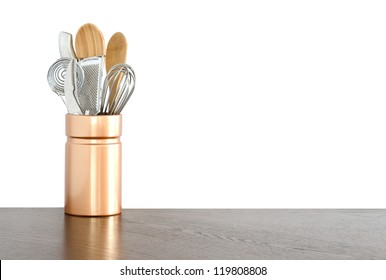 Kitchen utensils in a ceramic container on white background