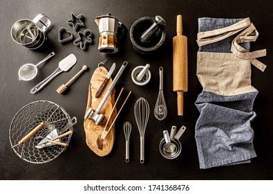 Kitchen utensils (cooking tools) and chef's apron on black chalkboard background. Kitchenware collection captured from above (top view, flat lay).