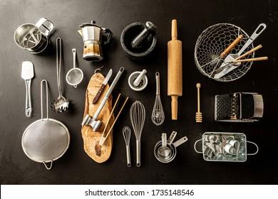 Küchenutensilien (Kochwerkzeuge) auf schwarzem Chalkboard-Hintergrund. Kochnische Sammlung von oben erfasst (oberste Ansicht, flache Lage).