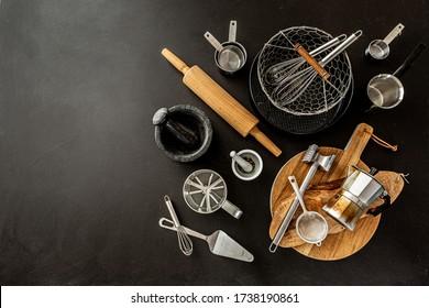 Küchenutensilien (Kochwerkzeuge) auf schwarzem Chalkboard-Hintergrund. Kochnische Sammlung von oben erfasst (oberste Ansicht, flache Lage). Layout mit freiem (Text-)Speicherplatz.