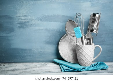 Kitchen utensils in cup on table against wall