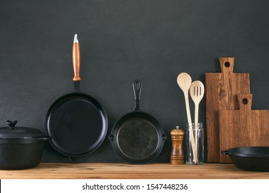 Kitchen utensils dark background with cast iron black kitchenware, front view of home kitchen table top