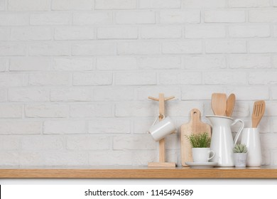 Kitchen utensils and dishware on wooden shelf. Kitchen interior background.Text space.