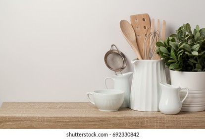 Kitchen utensils and dishware on wooden shelf. Kitchen interior background