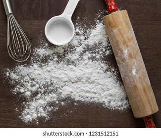 Kitchen utensils and flour, including roller pin, whisk and measuring scoop.