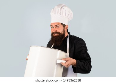 Kitchen utensils. Handsome male chef with saucepan. Chef man in hat holds pan. Man in chef uniform with saucepan. Bearded man cook in kitchen. Healthy food cooking. Chef cooking tasty dish in kitchen.