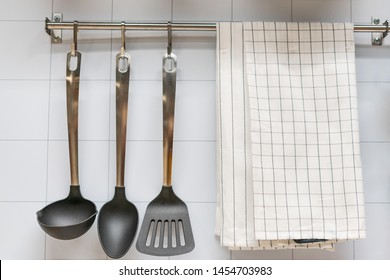 kitchen utensils hanging on the wall and towel.