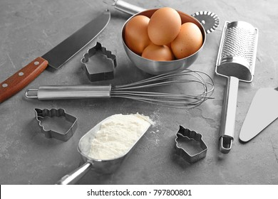Kitchen utensils and ingredients for pastries on grey background