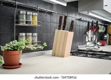 Kitchen utensils and jars of spices in hanging shelf in modern kitchen interior closeup