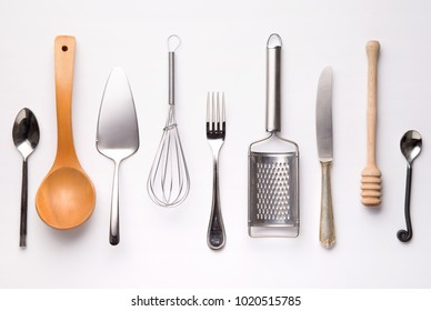 Kitchen utensils, metal and wooden, isolated on white background. Spoons, fork, knife, honey spoon, grinder, whisker. Top view