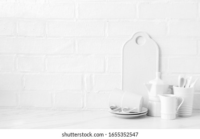 Kitchen utensils on a background of a white brick wall. Concept of the decor of the kitchen.Interior in bright colors. Text space.