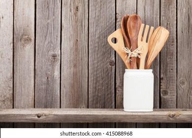 Kitchen utensils on shelf against rustic wooden wall