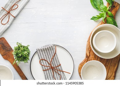 Kitchen utensils on a white table in a modern kitchen. Place for text. Top view.