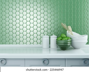 Kitchen utensils on the white worktop. Ceramic and glass kitchenware in front of modern green tile.
