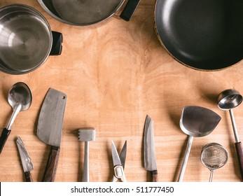 Kitchen utensils on wooden table background.