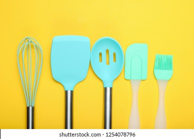 Kitchen utensils set : culinary brush, whisk, spatula on yellow background. Top view, minimalism