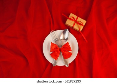 Kitchen utensils spoon and fork on red background, love, Valentine's day