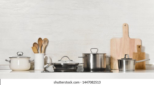 Kitchen utensils and stainless steel cookware front view, space for a text above
