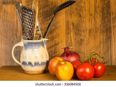 Kitchen Utensils in Stoneware pitcher against rustic wood wall surrounded by fruit and vegetables.