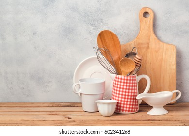 Kitchen utensils and tableware on wooden table over rustic background with copy space