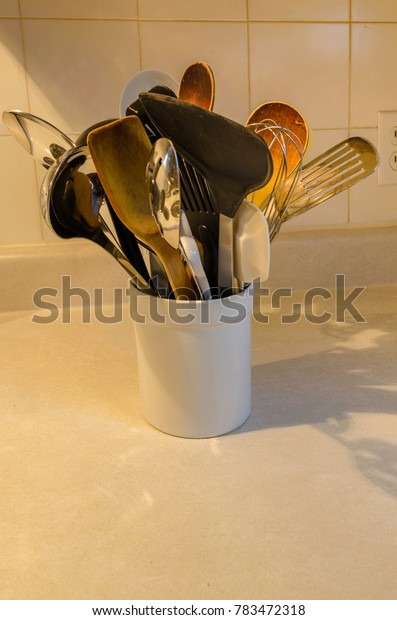 kitchen utensils in white ceraminc jar on countertop with ceramic tiles in the background