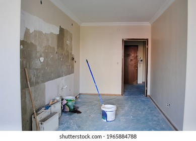 Kitchen wall during reconstruction work without door, tiles and tap. Left over dirty radiators with small tools. Home renovation improvement. Home repairing.