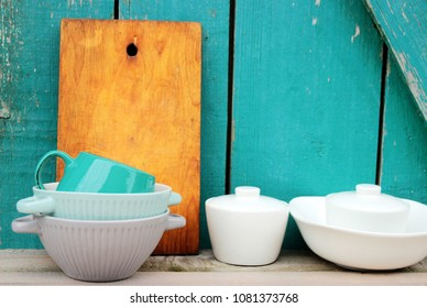 Kitchen ware set on bright turquoise wooden background, vintage crockery and chopping board , rustic design, eco concept. Shabby chic