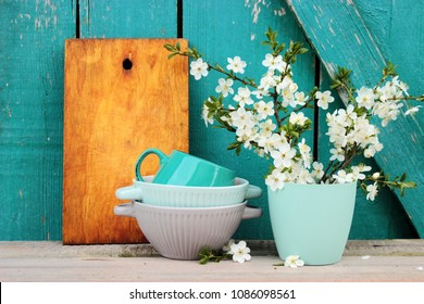Kitchen ware set on bright turquoise wooden background, vintage crockery, chopping board and beautiful spring bouquet in a simple case, rustic design. Shabby chic