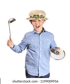 Kitchen warrior boy with a pot helmet on a head holding steel soup ladle as a sword and pot lid as a shield isolated on white background