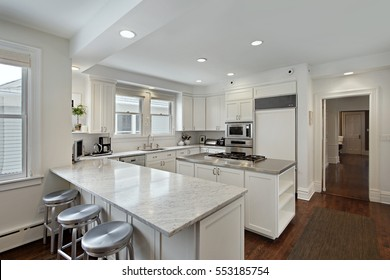 Kitchen with white cabinetry and stove-top island.