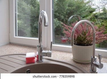 Kitchen with window, faucet , sink and a flower pot