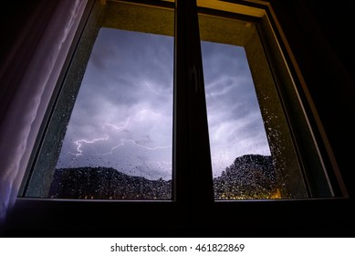 The kitchen window lights up during a thunderstorm as rain splashes against the window.
