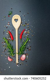 Kitchen wooden spoon with heart frame, pepper, peperoni, salt, rosemary, garlic, on dark  background, top view. Herbs and spices cooking top table
