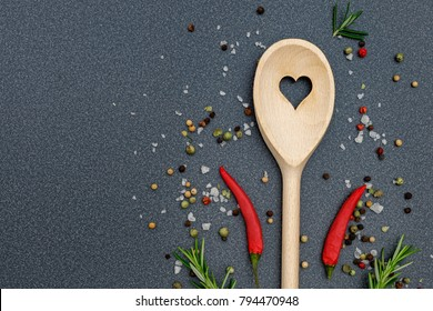 Kitchen wooden spoon with heart frame, pepper, peperoni, salt, rosemary,  on dark grey kitchen counter top  background, top view. Herbs and spices cooking background