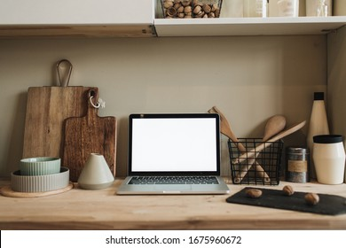 Kitchen workspace with blank copy space mock up laptop screen. Modern stylish kitchen interior design with wooden kitchenware. Front view blog, social media, website hero header template.