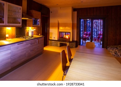Kitchen-dining room interior. Kitchen with dining table in evening. Evening light illuminates room. Dining room with fireplace. Private house kitchen. Exit to terrace in background.