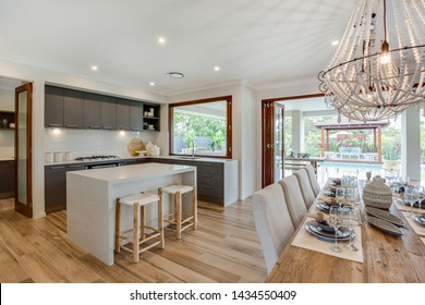 Kitchenette with a 2 seater snack counter adjacent to the dining table with beautiful chandeliers hanging over it and overlooking the pool area.