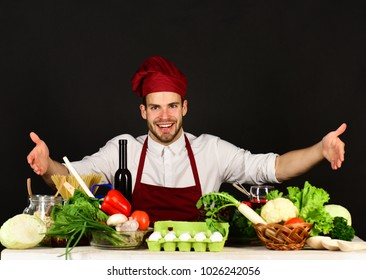 Kitchenware and cooking concept. Cook sits in kitchen near table with vegetables and tools. Man in burgundy hat and apron points at food. Chef with excited face on black background.
