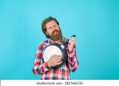 Kitchenware. Cooking vessels. Kitchen advertising. Bearded man play with frypan like guitar. Crazy chef with frypan. Cooking. Cooking utensils.