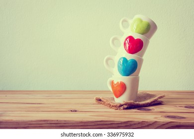 Kitchenware with cup of coffee on wooden table over grunge background,