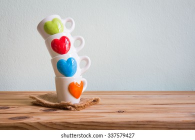 Kitchenware with cup of coffee on wooden table over grunge background