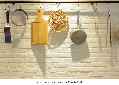 Kitchenware hang on white brick wall