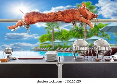 Kitchenware on table and Grilled pig on the broach on the beach