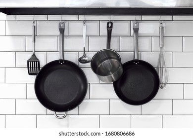 kitchenware, pans, bowls, with cutlery hanging on a white brick wall in a row