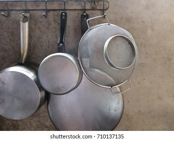 Kitchenware were hang on the stainless rack which attach with the old wall