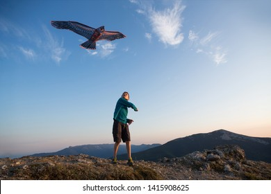 Kite flying. The boy launches a kite. Beautiful sunset. Mountains, sea, landscape. Summer day, sunny. eagle kite