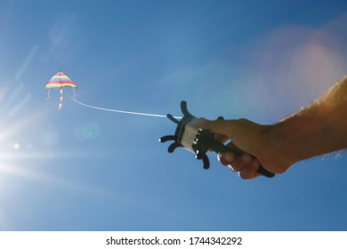 Kite flying in the clear blue sky. Hand holds tightly by the string of a kite. A man flying a kite on a clear sunny day.