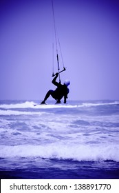 Kite surfer silhouette on blue sky background (blue tonned)