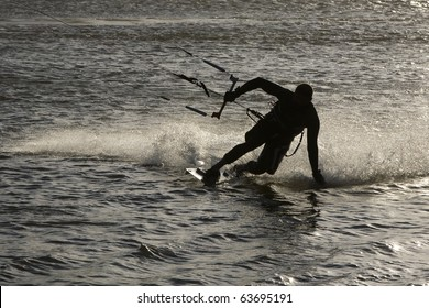 Kite surfer silhouette, sliding fast, feeling the water flow trough his hand, at the Obidos lagoon, Bom Sucesso, Foz do Arelho, Silver Coast, Portugal